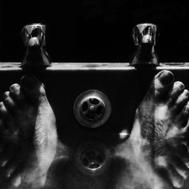 """Feet in bath with taps"" stock image"