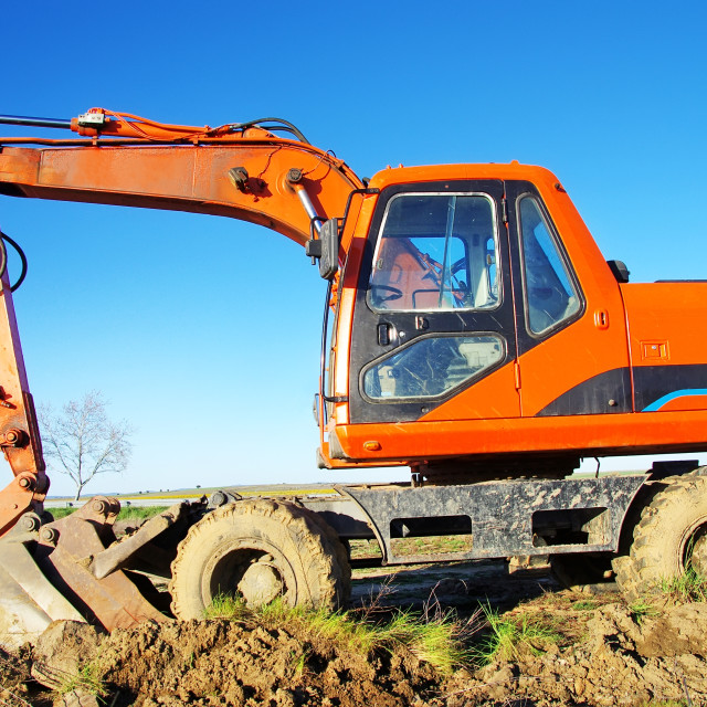 """Orange excavator on a working platform"" stock image"