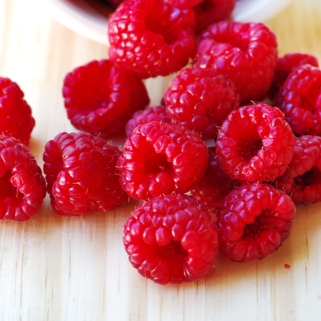 """Raspberries in a basket on wooden table"" stock image"