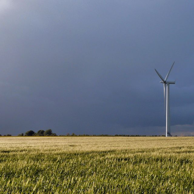 """A wind turbine ahead of a storm"" stock image"