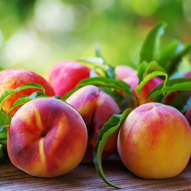 """Ripe peaches and leaves on table"" stock image"
