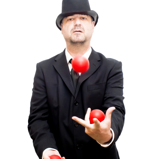 """Businessman with a hat that is juggling with a red balls"" stock image"