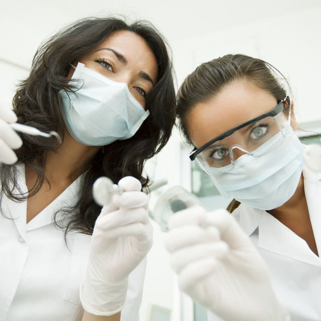 """Two Female Dentist looking at patient"" stock image"