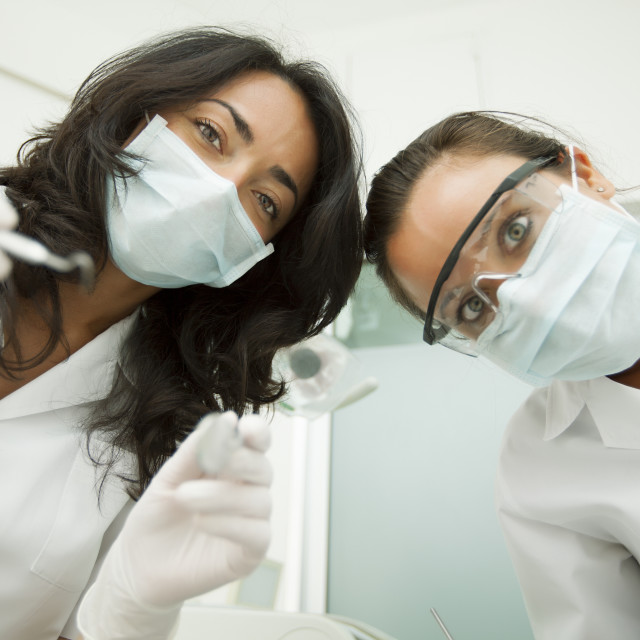 """Medical worker smiling and looking at patient"" stock image"