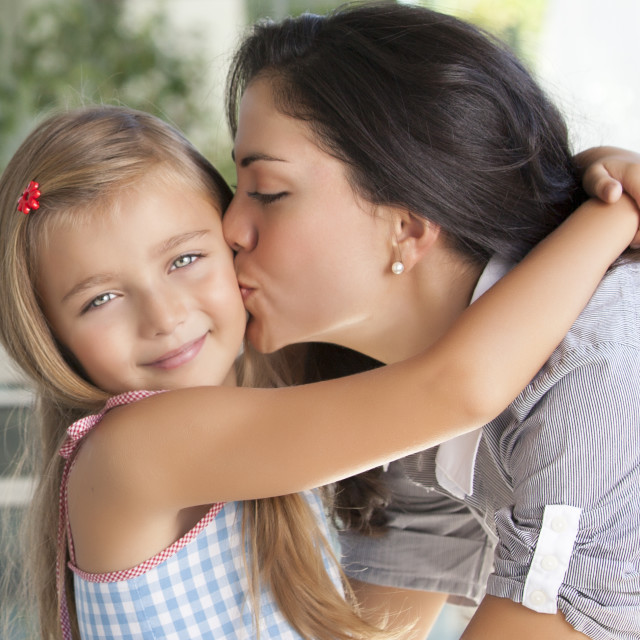 """Beautiful mother kissing her daughter"" stock image"