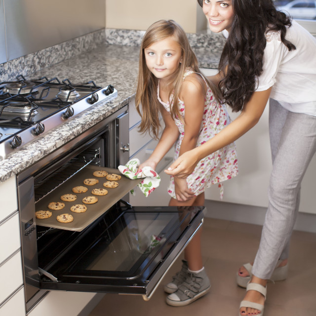 """Mother cooking with her daughter"" stock image"