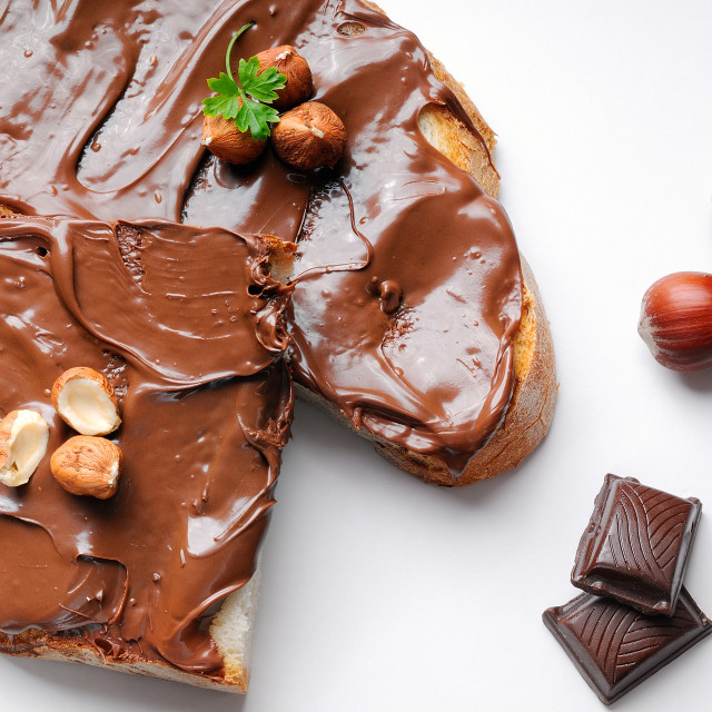 """""""Bread with chocolate cream and hazelnuts isolated top view"""" stock image"""