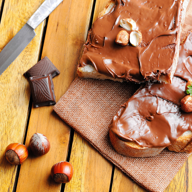 """""""Bread with chocolate cream and hazelnuts on a table top"""" stock image"""