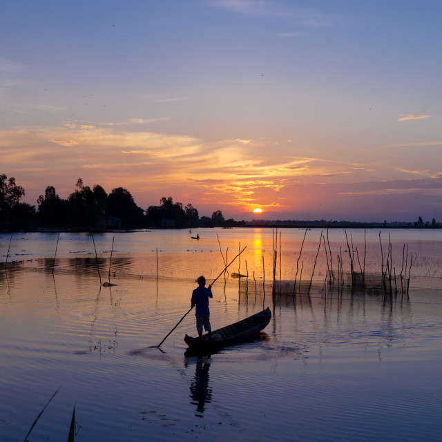 """Fisher man working on the fishing farmland at sunrise"" stock image"