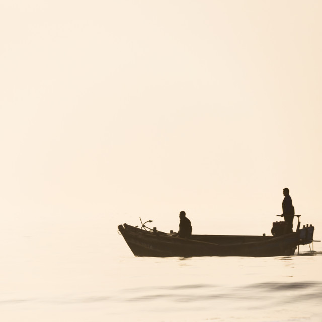 """""""Two fishermen in their boat in glassy calm seas at dawn in China"""" stock image"""
