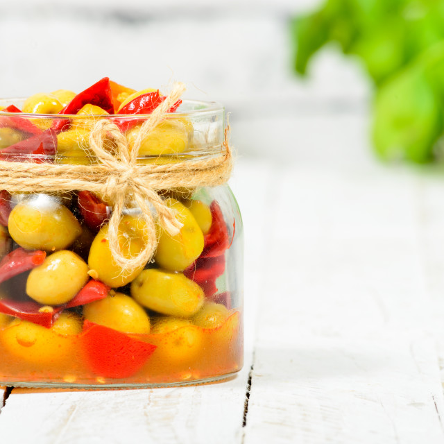 """glass jar with olives and peppers on white table"" stock image"