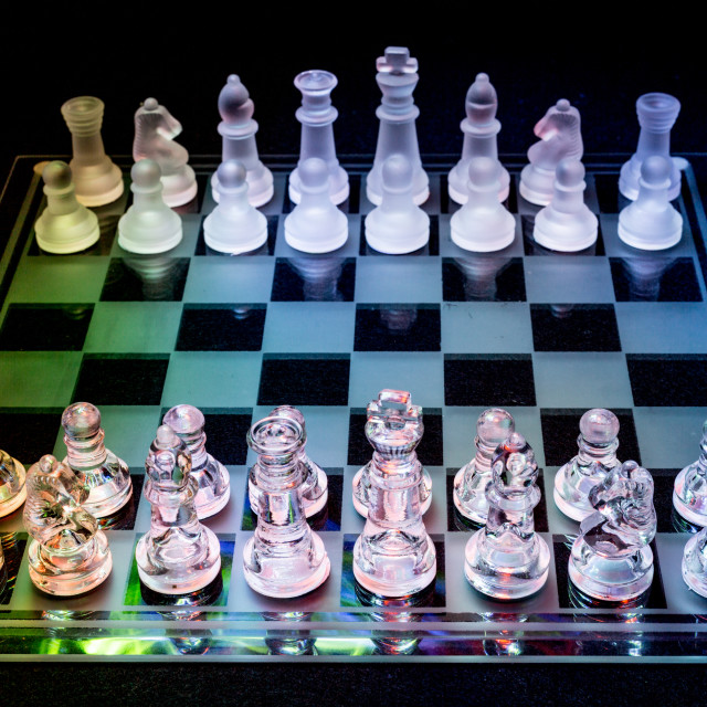 """Glass Chess Set Under Coloured Lights"" stock image"