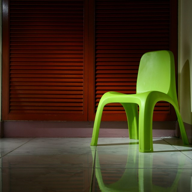 """""""Green plastic chair in a room"""" stock image"""