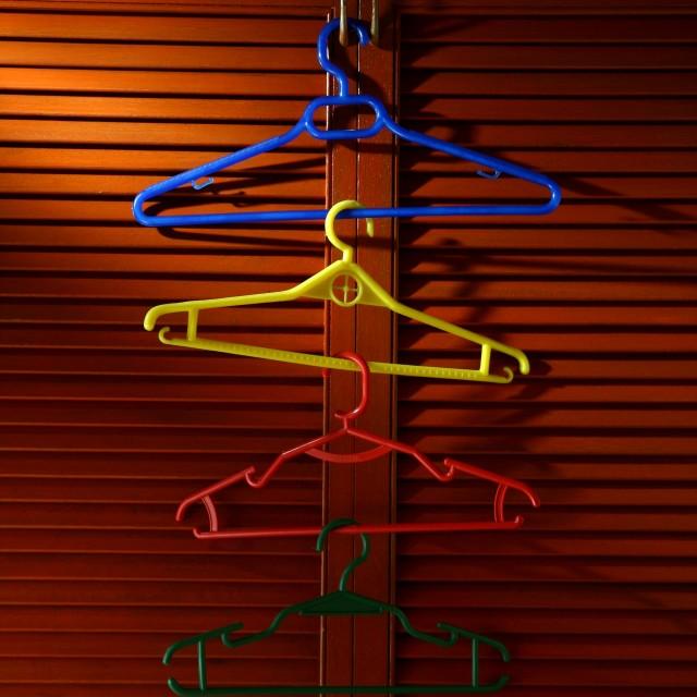 """""""Wooden cabinet door with linked hangers on its metal handle"""" stock image"""