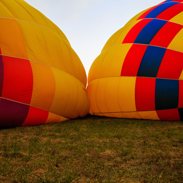 """Two hot air balloons on ground being inflated"" stock image"