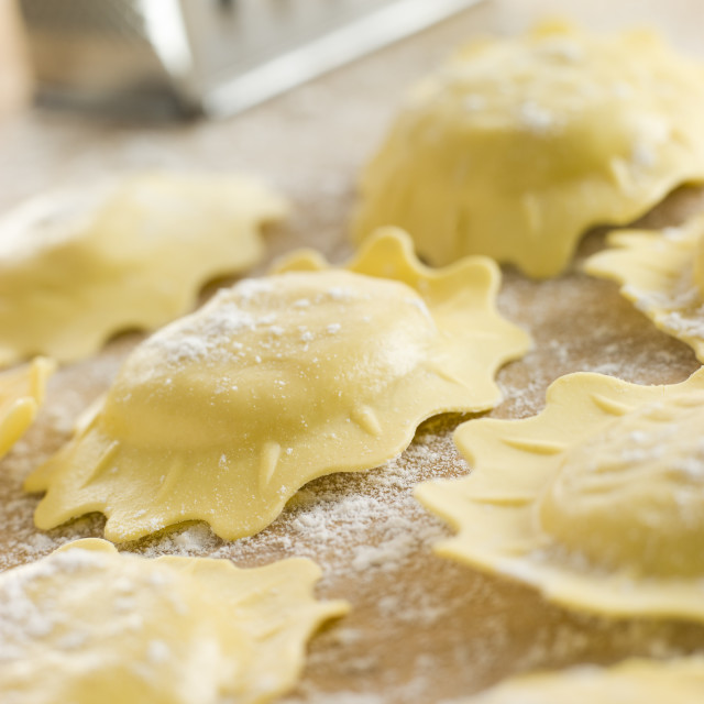 """Uncooked Spinach and Ricotta Ravioli on a floured surface"" stock image"