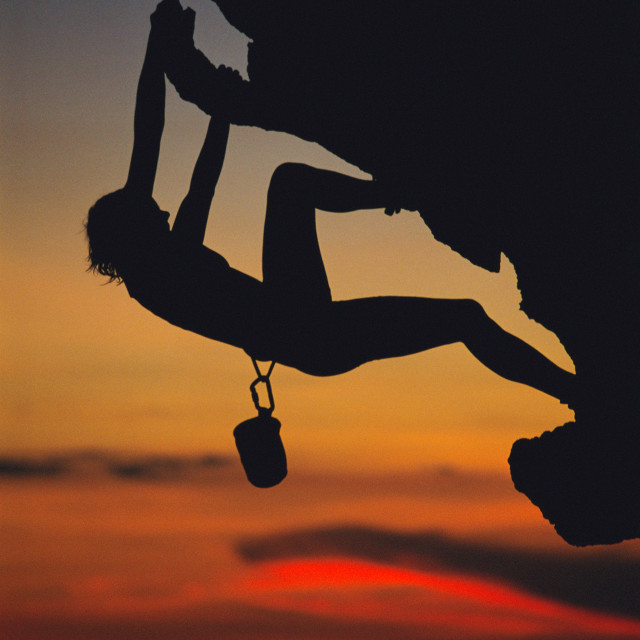 """A young woman climbing up a rock face"" stock image"