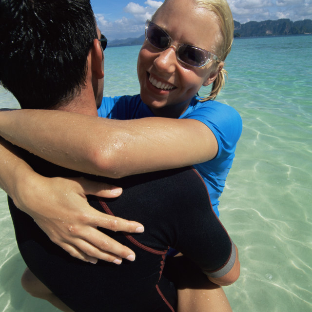 """Couple embracing in water at beach"" stock image"