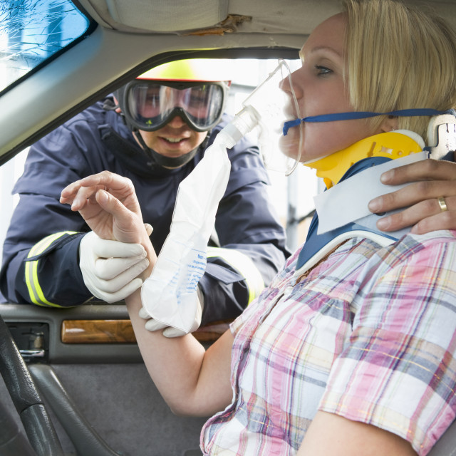 """Firefighters helping an injured woman in a car"" stock image"