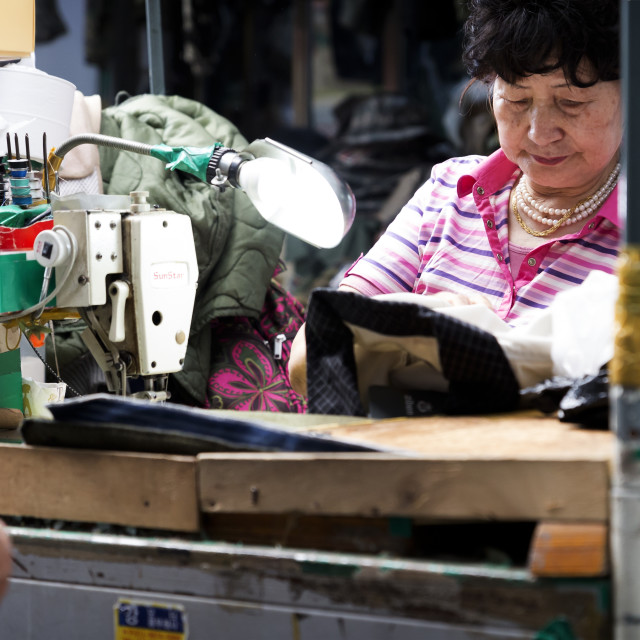 """Seamstress at work at Seoul's Kwang Jang Market, South Korea"" stock image"