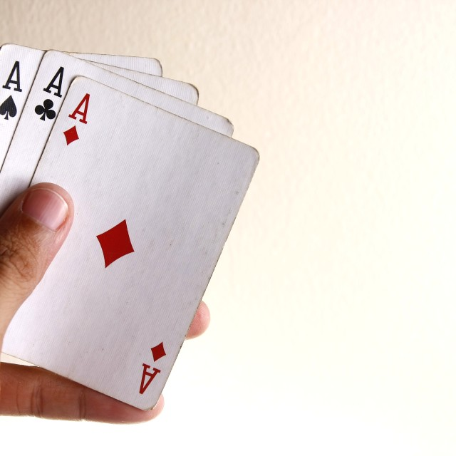 """Hand holding Four aces of a playing card deck"" stock image"