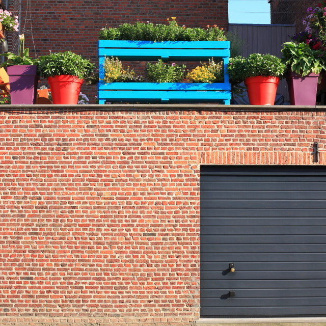 """Garage with colourful plant pots"" stock image"