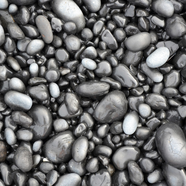 """Black lava pebbles on beach"" stock image"