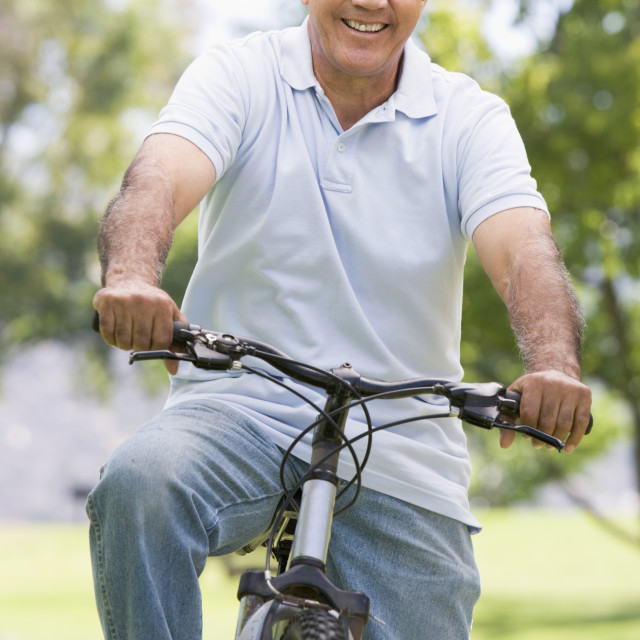 """Man on bike outdoors smiling"" stock image"