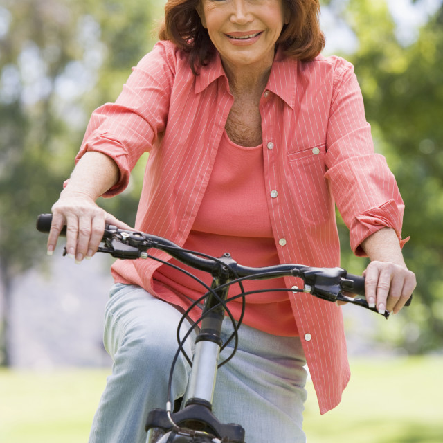 """""""Woman on bike outdoors smiling"""" stock image"""