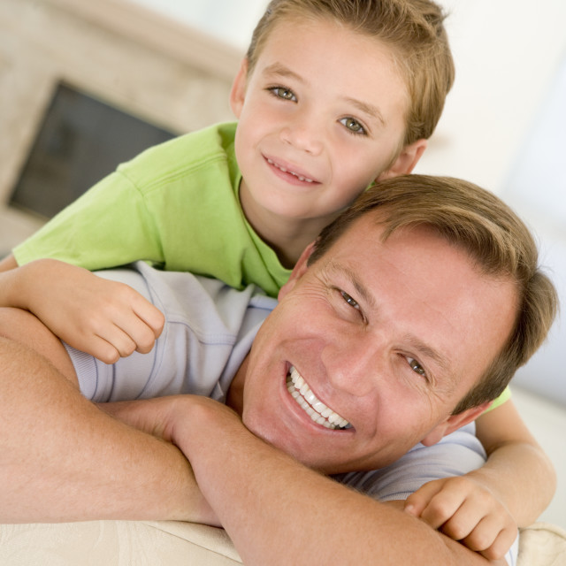 """""""Man and young boy sitting in living room smiling"""" stock image"""