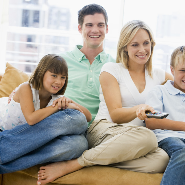 """""""Family sitting in living room with remote control smiling"""" stock image"""