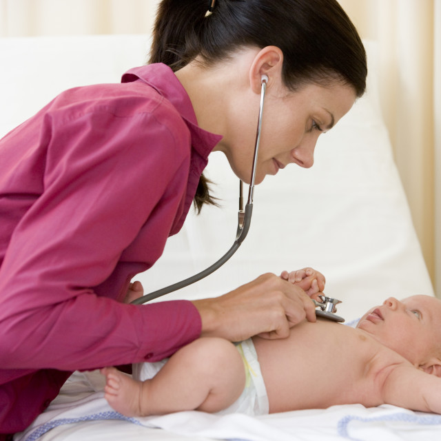 """Doctor giving checkup with stethoscope to baby in exam room"" stock image"