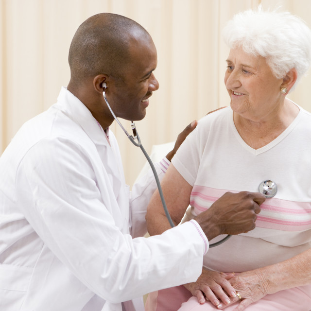 """""""Doctor giving checkup with stethoscope to woman in exam room smiling"""" stock image"""