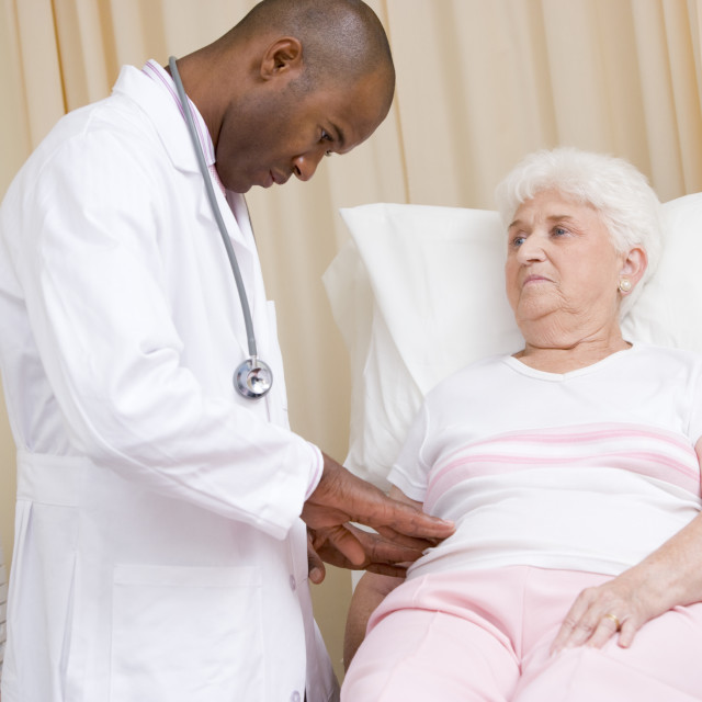 """""""Doctor giving checkup to woman in exam room"""" stock image"""