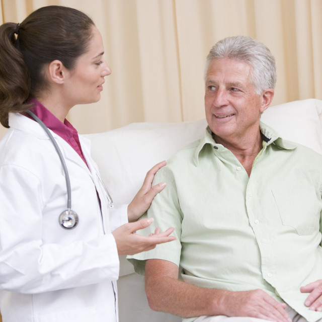 """""""Doctor giving checkup to man in exam room smiling"""" stock image"""