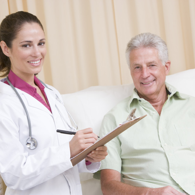 """""""Doctor writing on clipboard while giving checkup to man in exam room smiling"""" stock image"""