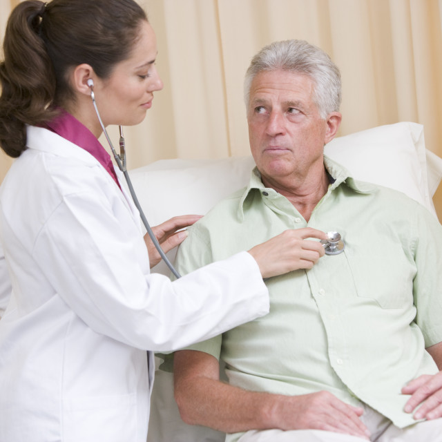 """""""Doctor giving checkup with stethoscope to man in exam room"""" stock image"""