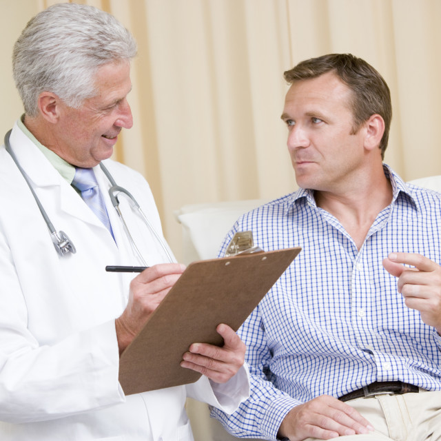 """""""Doctor writing on clipboard while giving man checkup in exam room"""" stock image"""