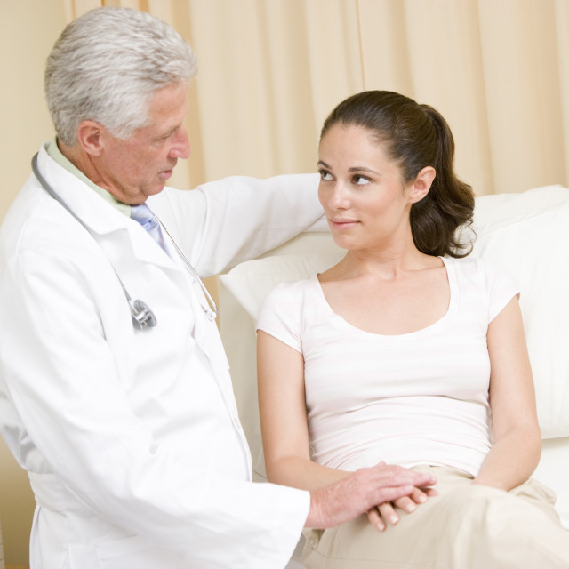 """""""Doctor giving woman checkup in exam room"""" stock image"""