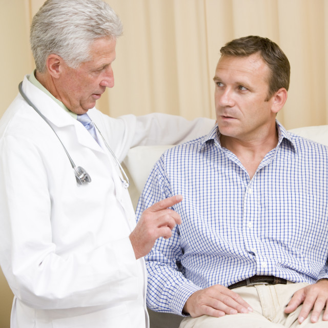 """""""Doctor giving man checkup in exam room"""" stock image"""
