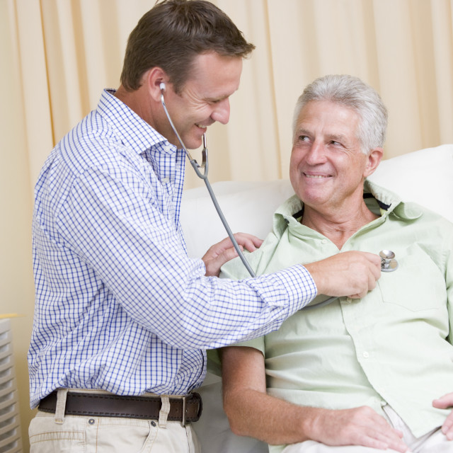 """""""Doctor giving man checkup with stethoscope in exam room smiling"""" stock image"""