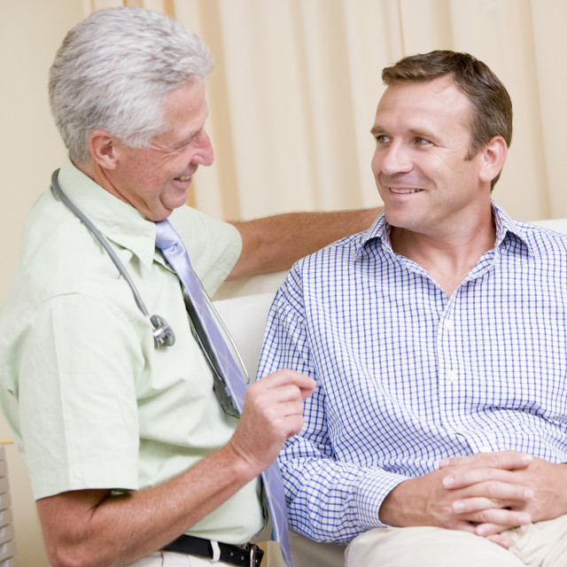"""""""Doctor giving smiling man checkup in exam room"""" stock image"""