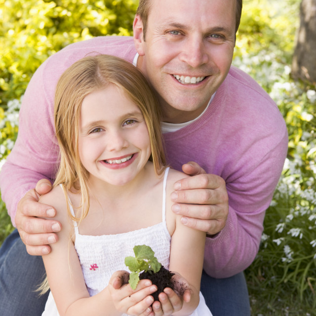 """""""Father and daughter outdoors holding plant smiling"""" stock image"""