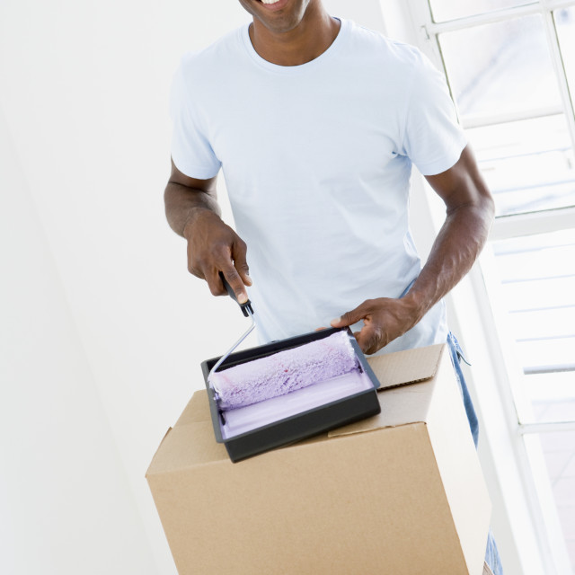 """""""Man with roller and paint in new home smiling"""" stock image"""