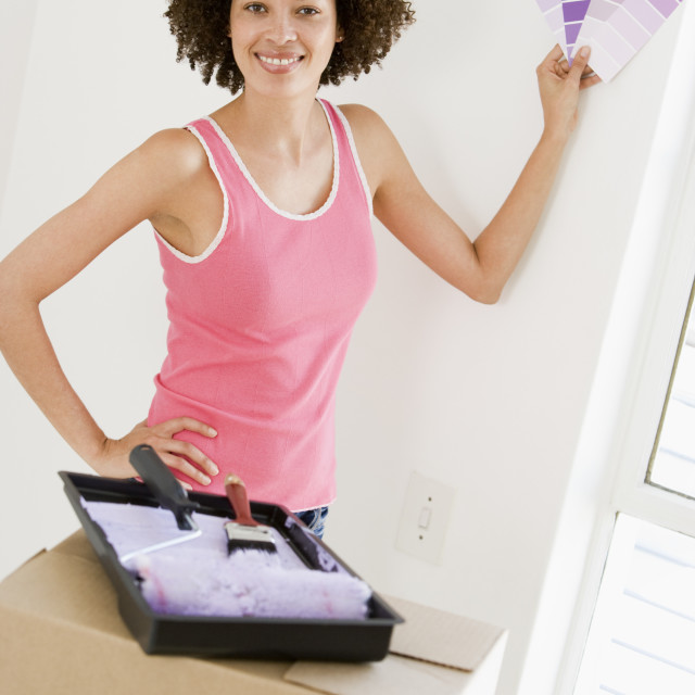 """""""Woman with paint swatches in new home smiling"""" stock image"""