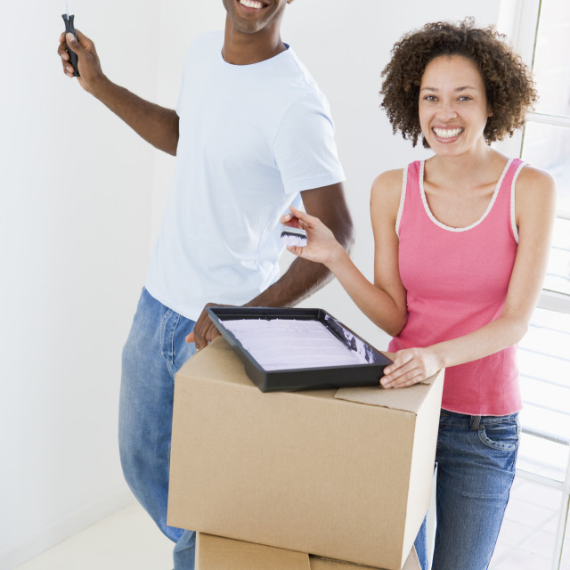 """""""Couple with roller and paint in new home smiling"""" stock image"""