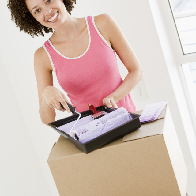 """""""Woman with roller and paint in new home smiling"""" stock image"""
