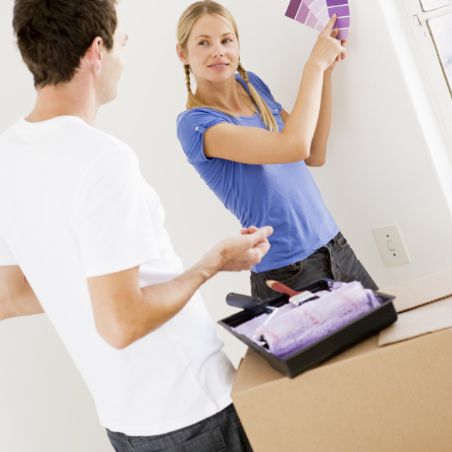 """""""Couple with paint swatches in new home smiling"""" stock image"""