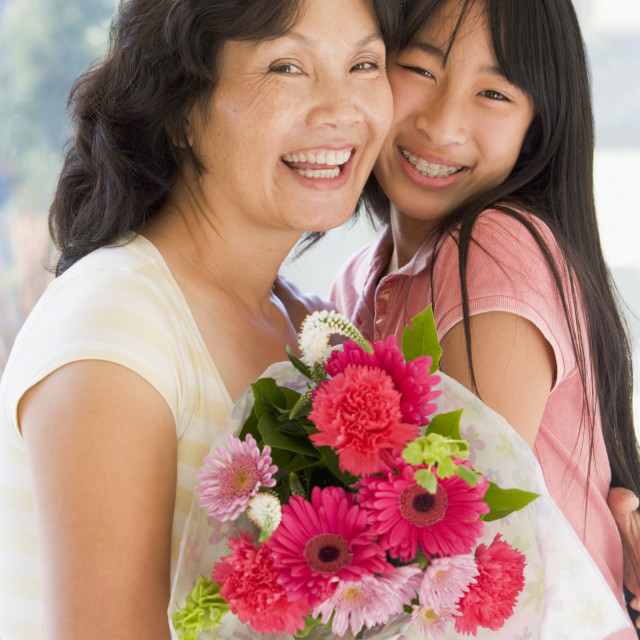 """""""Granddaughter and grandmother holding flowers and smiling"""" stock image"""