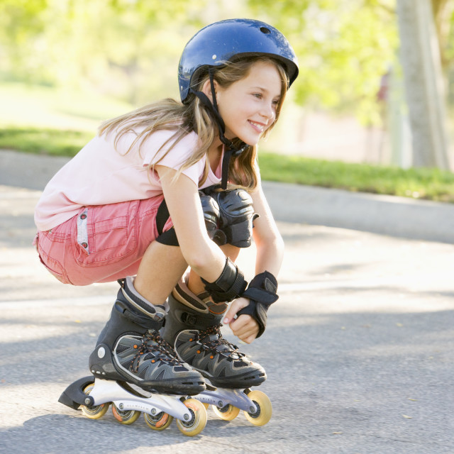 """Young girl outdoors on inline skates smiling"" stock image"
